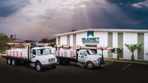 Budget Roofing Supply In Front of Warehouse with two loaded trucks (1)